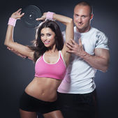 Athletic man and woman doing fitness exercise — Stock Photo