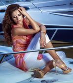 Young cute brunette girl sitting on the yacht. — Stock Photo