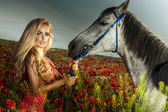 Attractive blonde woman posing with horse — Stock Photo