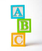 Wooden alphabet blocks stacked — Stock Photo