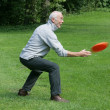 Stock Photo: Senior man playing with a frisbee