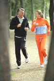 Couple jogging through the park — Stock Photo