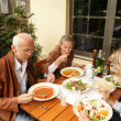 Middle-aged friends enjoying a meal — Stock Photo