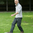 Senior man kicking a ball — Stock Photo