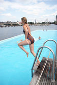 Shapely woman jumping from a diving board — Stock Photo