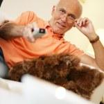 Elderly man watching television — Stock Photo