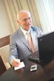 Senior hombre trabajando en un ordenador portátil — Foto de Stock