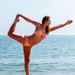 Fit woman in a bikini doing yoga at the seaside — Stock Photo #39877257