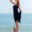 Beautiful woman playing lookout at the seaside — Stock Photo