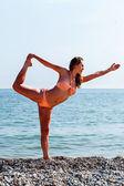 Fit woman in a bikini doing yoga at the seaside — Stock Photo