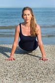 Beautiful tanned woman doing press ups at the sea — Stock Photo