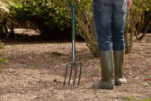 Man working in the garden carrying a fork — Stock Photo