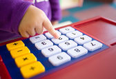 Kids finger pressing toy calculator — Stock Photo