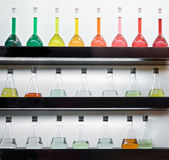 Colorful liquid in flasks laying on shelf — Stockfoto