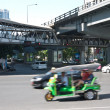 Tuk-tuk driving in business area of bangkok — Stock Photo