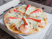 Seafood pizza in the paper box — Stock Photo