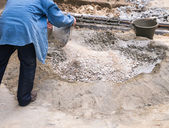 Worker mixing concrete in construction area — Foto Stock