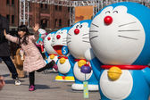 Child takes photo with Doraemon figure — Stock Photo