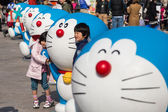 Children takes photo with Doraemon figure — Stock Photo