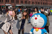 Girls take photo with Doraemon figure — Stock Photo