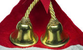 Real christmas bells on red cloth — Stock Photo