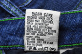 Wash care instructions on jeans — Stock Photo