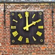 Clockwork in old wall with roman numerals — Stock Photo
