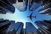 Torri di affari con una silhouette di aeroplano — Foto Stock