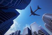 Torres de negócios com uma silhueta de avião — Foto Stock
