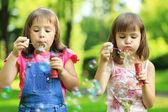 Little girls blowing soap bubbles — Stock Photo