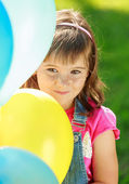 Little happy girl holding colorful balloons in green park — Stock Photo