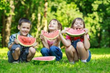 Happy smiling children eating fruits in park