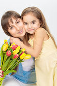 Happy mother and daughter with flowers — Stock Photo