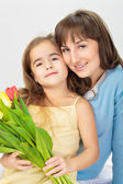 Picture of mother and daughter with flowers — Stock Photo
