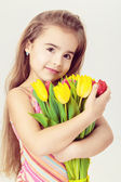 Beautiful little girl with fair hair in a pink dress holds flowers — Stock Photo