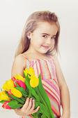Bel enfant avec des cheveux blonds dans une robe rose détient fleurs — Photo