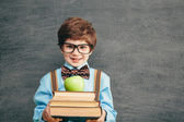 Little boy with books and apple — Stock Photo