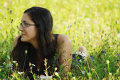 Beautiful young woman lies on green grass — Stock Photo
