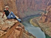 A beautiful woman sitting on a cliff. — Stock Photo