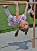 A cute girl playing on bars. — Stock Photo