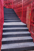 Black staircase and red fence — Stock Photo