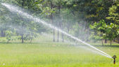 High pressure water sprinkle working in public park — Stock Photo