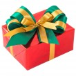 Red gift box with green and gold bow tie — Stock Photo
