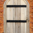 Wooden door on brick wall — Stock Photo
