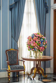 Elegance armchair and flower bouquet on table — Stock Photo