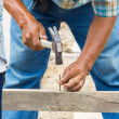 Stock Photo: Worker hammering nail into wood