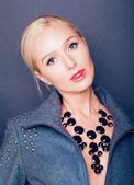 The stylish blonde looks in a shot and at breasts big decoration of a necklace — Stock Photo