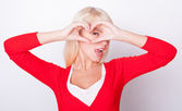 Blonde girl made heart and smiles — Stock Photo