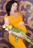 Beautiful pregnant girl with bouquet of tulips — Stock Photo