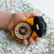 Compass on the map holding a child's hand. — Stock Photo